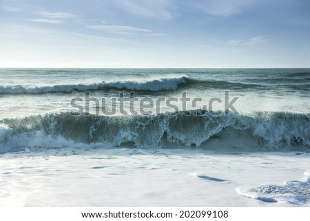 Beautiful surf in the early morning with waves coming in - stock photo