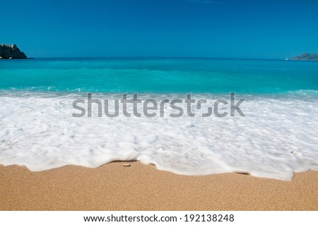 Beautiful surf on the beach. Mountains on the horizon. - stock photo