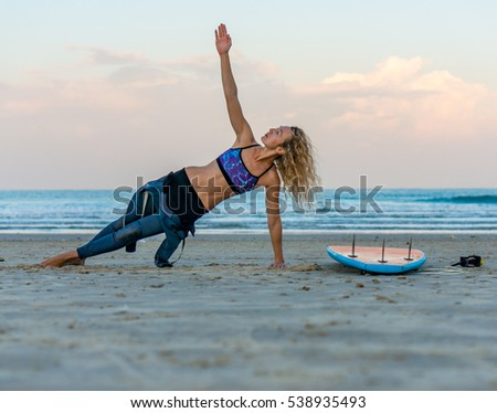 Beautiful surfer girl stretching on the beach. She look up