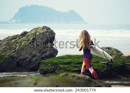 Beautiful surfer girl walking in the beach carrying her surfboard - stock photo
