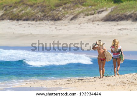 Beautiful surfer girls walking on the beach - stock photo