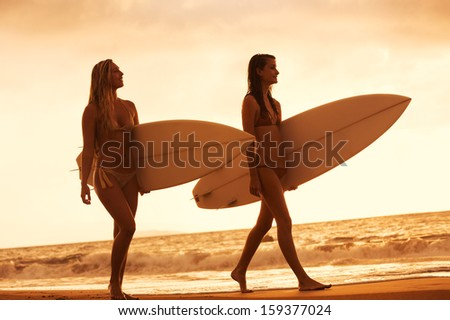 Beautiful Surfer Girls Walking on the Beach at Sunset in Hawaii - stock photo
