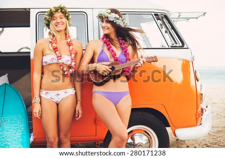 Beautiful Surfer Girls with Ukulele and Flower Leis hanging out on the Beach at Sunset with Classic Vintage Surf Van - stock photo