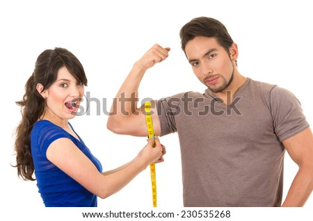 beautiful surprised girl holding measuing tape around handsome muscular man's arm biceps isolated on white - stock photo