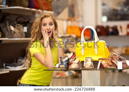 Beautiful surprised girl with yellow bag in a store shopping bags. Shopping - stock photo