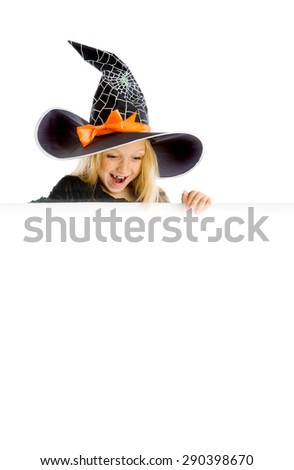 Beautiful surprised little girl with long blonde hair in the witch costume looking down the sign. Black witch hat with web, spider and orange bow. Copy space. - stock photo
