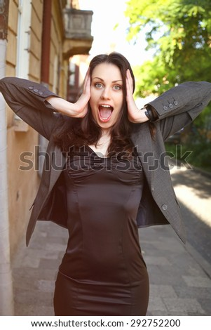 Beautiful surprised woman. Office worker. Office clerk in shock. The stress of the business world. Business fashion business style. Business woman on the street. Shock, surprise, stress. - stock photo