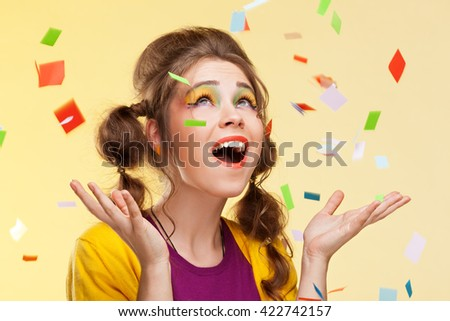 Beautiful surprised woman stretching out her hands while confetti falling on her