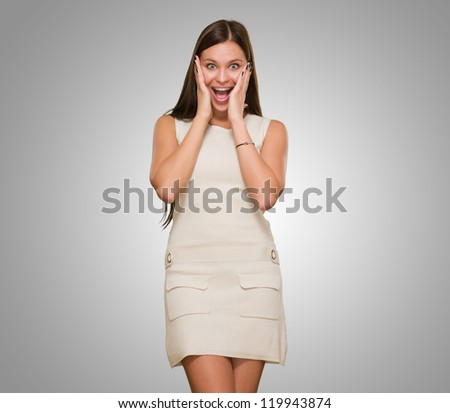 Beautiful Surprised Young Woman against a grey background - stock photo
