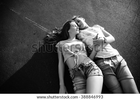 Beautiful sweet couple lying on the asphalt  and hugging on the street during sunset. Black and white