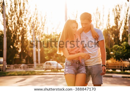 Beautiful sweet couple riding on roller skates holding hands on the street during sunset. - stock photo