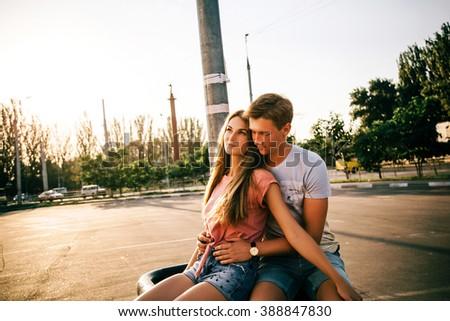 Beautiful sweet couple sitting on the street during sunset. Guy hugs girl - stock photo