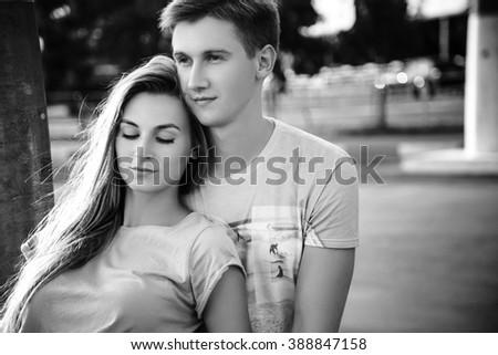 Beautiful sweet couple sitting on the street during sunset. Guy hugs girl. Black and white - stock photo
