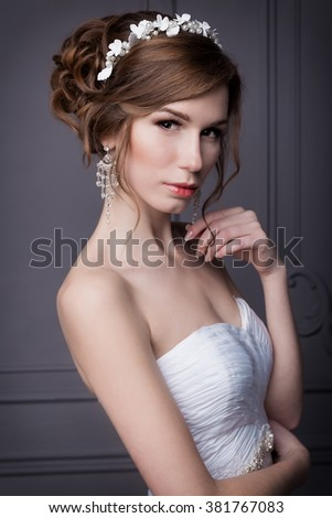 beautiful sweet gentle girl groom in a wedding dress with a wreath and flowers in her hair in the studio