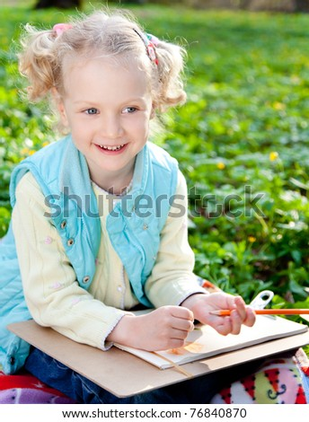 Beautiful sweet girl in the park drawing pencil