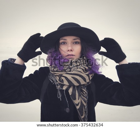 Beautiful sweet girl with a lilac hair in a black hat, coat and scarf posing against the backdrop of the frozen Gulf of Finland in St. Petersburg. - stock photo