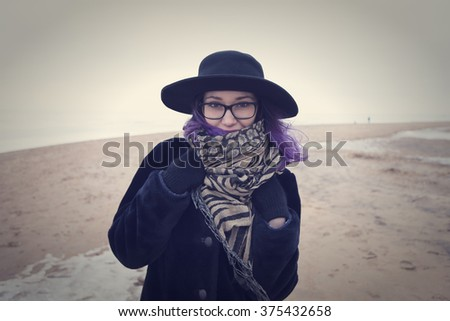 Beautiful sweet girl with a lilac hair in glasses, coat and scarf posing against the backdrop of the frozen Gulf of Finland in St. Petersburg. - stock photo
