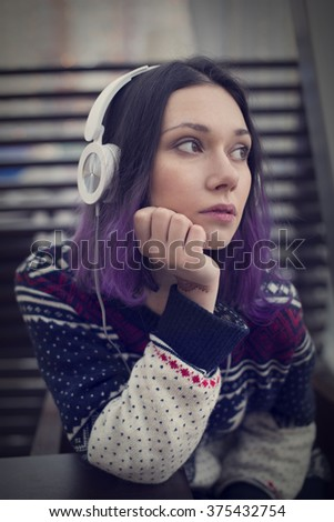 Beautiful sweet girl with blue hair and white headphones sitting in a room and listen to music. - stock photo