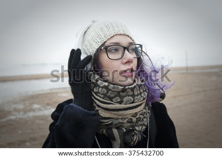 Beautiful sweet girl with blue hair wearing glasses, a white cap, coat and scarf listening to music on headphones white against the backdrop of the frozen Gulf of Finland in St. Petersburg. - stock photo