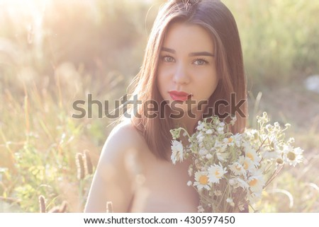 beautiful sweet girl with full lips sitting in a field with a bouquet of daisies with obnozhennymi shoulders at sunset in the sunlight