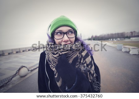 Beautiful sweet girl with violet hair, glasses, green hat, coat and scarf listening to music on headphones white walking on the road along the beach in St. Petersburg. - stock photo