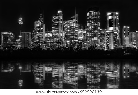 Beautiful Sydney Skyline at night in black and white of Central Business District seen from Farm Cove, with reflections in bay's water.