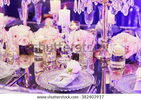 Beautiful table set with candles and flowers for a festive event, party or wedding reception, in purple light