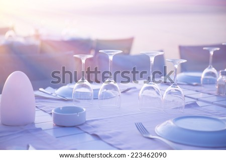 Beautiful table setting on the wedding, empty crystal wineglasses, expensive banquet on the beach, luxury outdoors restaurant  - stock photo