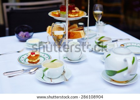 Beautiful table setting with selection of sandwiches, fancy cakes, tea and champagne served for the ceremony of afternoon tea - stock photo