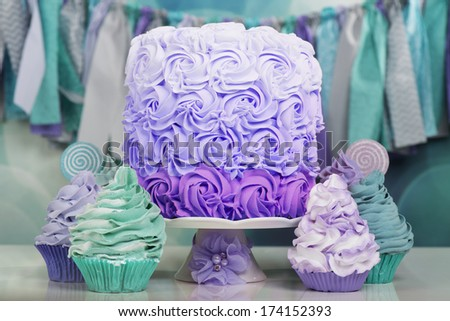 Beautiful table with cake and cupcakes in aqua and purple