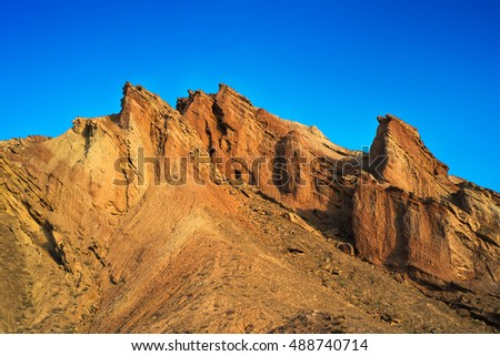 Beautiful tall mountains in Central Asia in wonderful colors at sunrise. Landscape does even more gorgeous with deep blue sky.