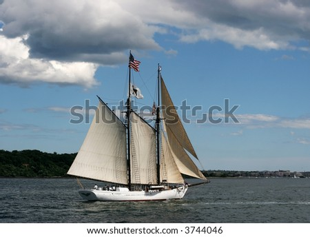 beautiful tall ship on ocean with blue sky and white puffy clouds