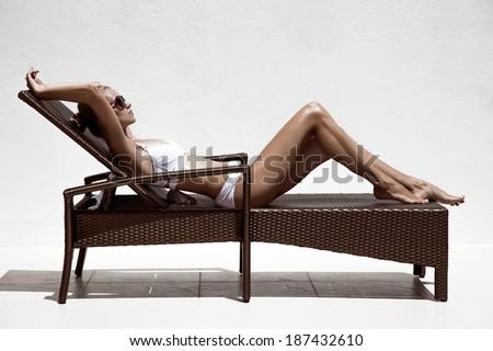 Beautiful tan female model sunbathing in bikini on chaise-longue. Against white wall.  - stock photo