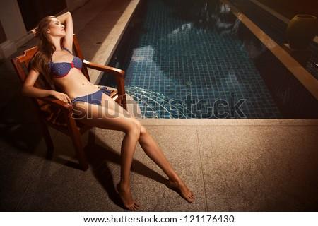 Beautiful tan woman in bikini sunbathing - stock photo