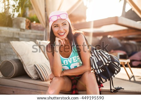 Beautiful tanned cheerful funny cheeky hipster girl sits in a cafe on the beach, enjoying the morning sun, dressed in casual clothes, nice smile, relax on a tropical island, lifestyle, happy - stock photo