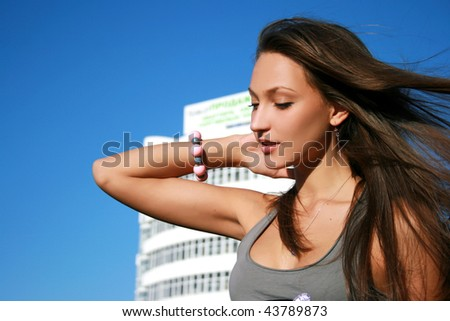 Beautiful tanned girl in urban landscape
