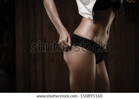 Beautiful tanned legs and buttocks of young woman on wooden background