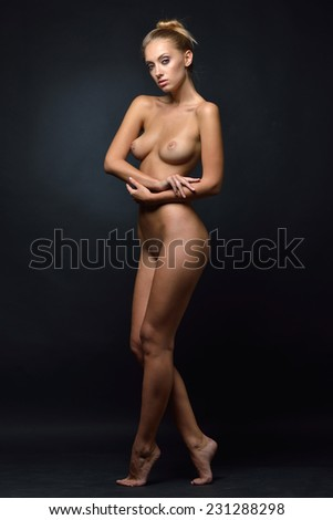 Beautiful tanned naked blonde woman posing in a dark Studio - stock photo