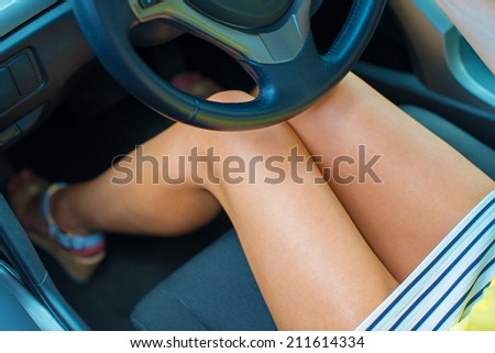 Beautiful tanned slim legs in a car. - stock photo