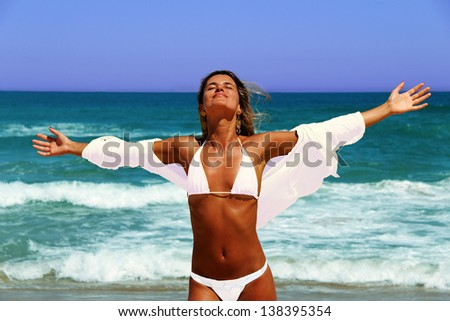 Beautiful tanned woman enjoying the sun on beach. - stock photo
