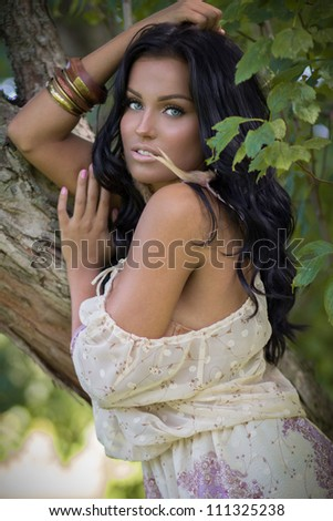 Beautiful tanned woman posing in the beige dress near the tree - stock photo