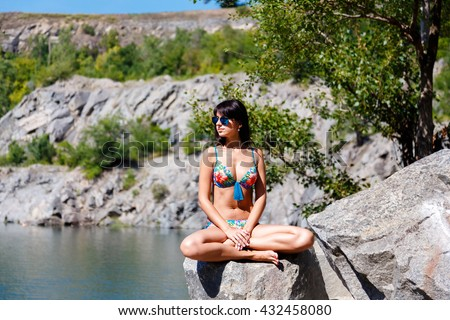 Beautiful tanned woman sitting in the lotus position in the mountains beach on sunny summer day