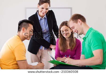 Beautiful teacher helping her students with homework - stock photo