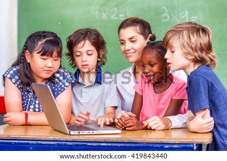 Beautiful teacher with mixed race classroom. - stock photo
