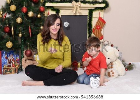 Beautiful teen girl and little boy play and wait for a New Year next to a Christmas tree