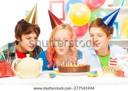 Beautiful teen girl blow cake on birthday party - stock photo