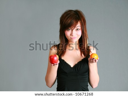 beautiful teen girl holding apple and orange - stock photo