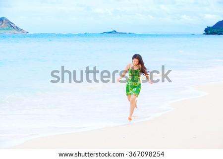 Beautiful teen girl in green dress running along Hawaiian beach at water's edge - stock photo
