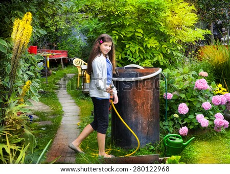 beautiful teen girl in the summer grin floral blossom garden with water hose