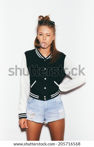 Beautiful teen girl inflating bubble of chewing gum and winking. Modern fashion girl. Toned.  White background, not isolated - stock photo